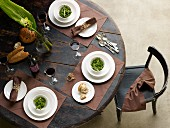 Place settings with small bowls of salad on brown place mats on round wooden table