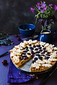 Almond and blackberry tart, sliced, with a jug of vanilla sauce