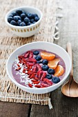 A bowl of smoothie with blueberries, desiccated coconut, goji berries, raspberries and clementines
