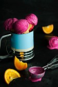 Raspberry ice cream in cones with an ice cream scoop and orange wedges