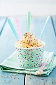 Vanilla ice cream with coloured sugar sprinkles in a paper ice cream tub with spoons