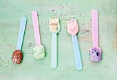Various types of ice creams on ice cream spoons scattered with sugar pearls: vanilla, strawberry, chocolate, blueberry and mint