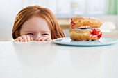 The little girl looking over the edge of a table at plate of doughnuts