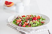 A summer salad with lamb's lettuce, strawberries, grapefruit, mint and sheep's cheese