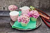 Carnations in cupcake cases and polka-dot mug and milk jug on tray