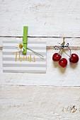 Dankeskarte und drei rote Kirschen aufgehängt an Schnur