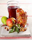 An arrangement of fresh fruit, hazelnuts and red wine