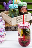 Mit Früchten und Kräutern aromatisiertes Wasser in Einmachgläsern