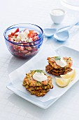 Courgette and salmon fritters with crème fraîche and dill served with a tomato and feta cheese salad