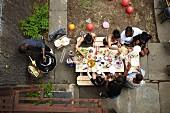 Blick von Oben auf Gruppe von jungen Leuten beim Grillen im Hinterhof