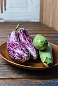 Aubergines and courgettes in a wooden bowl on a wooden surface