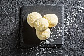 White coconut pralines on a black stone