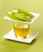 A glass of olive oil and sliced green apple