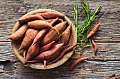 Sweet potatoes in a wooden bowl with sprigs of rosemary