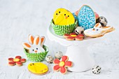 Colourful Easter biscuits and quails egg's on a cake stand