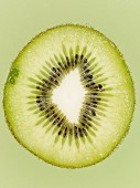 A slice of kiwi on the green surface, close-up