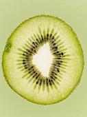 Aufgeschnittene grüne Kiwi vor grünem Hintergrund, Close-Up