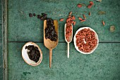 Dried cranberries and goji berries in wooden scoops and bowls on a rustic wooden surface