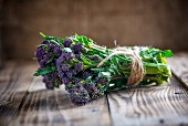 A bundle of purple sprouting broccoli on a wooden board