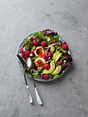 A mixed leaf salad with avocado, raspberries, goat's cheese and pine nuts