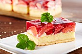 A slice of strawberry cake garnished with a strawberry leaf