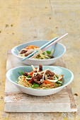Pork chop suey with vegetables, sesame seeds and ginger on a bed of noodles