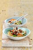 Schweinefleisch Chop Suey mit Gemüse, Sesam und Ingwer auf Nudeln