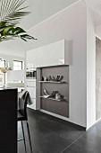 Massgefertigte Küchenschränke zum Teil in Wand eingebaut, Ablagen an Wand in offener Küche