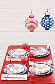 Outdoor table set for Fourth of July below paper lanterns (USA)