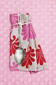 Vintage Löffel auf Leinen Serviette mit Blumenmuster auf rosa Tischset