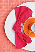 Knotted linen napkin and orange cup on white plate