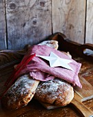 Two light rye breads under a tea towel and a Christmas decoration