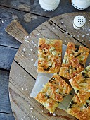 Focaccia topped with vegetables and coarse sea salt on a wooden board (top view)