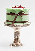 A green wedding cake on a silver cake stand