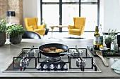 Kücheninsell mit Betonarbeitsplatte und Gaskochfeld, Pfanne mit Kartoffelburger