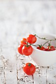 Cherry tomatoes in a white bowl on a white wooden surface