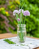 Flowering chives in a glass of water on a garden table