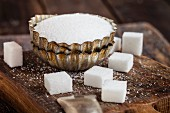 A bowl of white sugar with sugar cubes in front of it