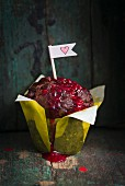 Chocolate muffin with raspberry sauce and paper flag