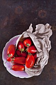 San Marzano tomatoes with a paper bag in a porcelain bowl