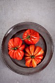 Three beefsteak tomatoes on a metal plate (seen from above)