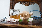 A jar of quince jelly on an antique chest of drawers with a mirror