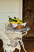 A basket of fresh squash and courgettes on an antique, white patio table