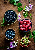 Bowls of fresh summer berries (raspberries, gooseberries and blueberries)