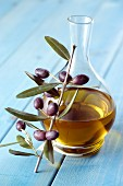 A carafe of olive oil and a sprig of olives