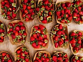Cardboard punnets of wild strawberries at an organic market