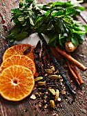 Various ingredients for hot drinks (oranges, spices, ginger, sugar, mint)