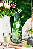 Mineral water with fresh herbs in a glass carafe on a garden table