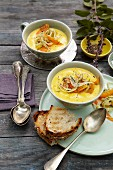 Creamy carrot soup topped with carrot and fennel