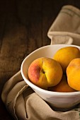 Peaches in a ceramic bowl on a wooden surface